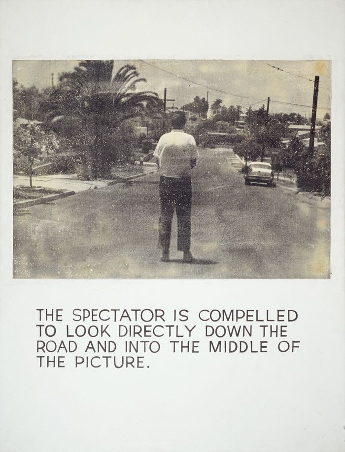 Monochrome painting of a man looking down a road, with hand-lettered text below: The spectator is compelled to look directly down the road and into the middle of the picture.