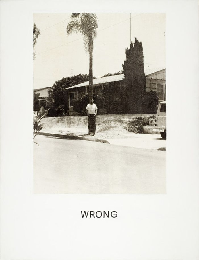 Monochrome painting of a man standing in front of a palm tree, with hand-lettered text below: Wrong.